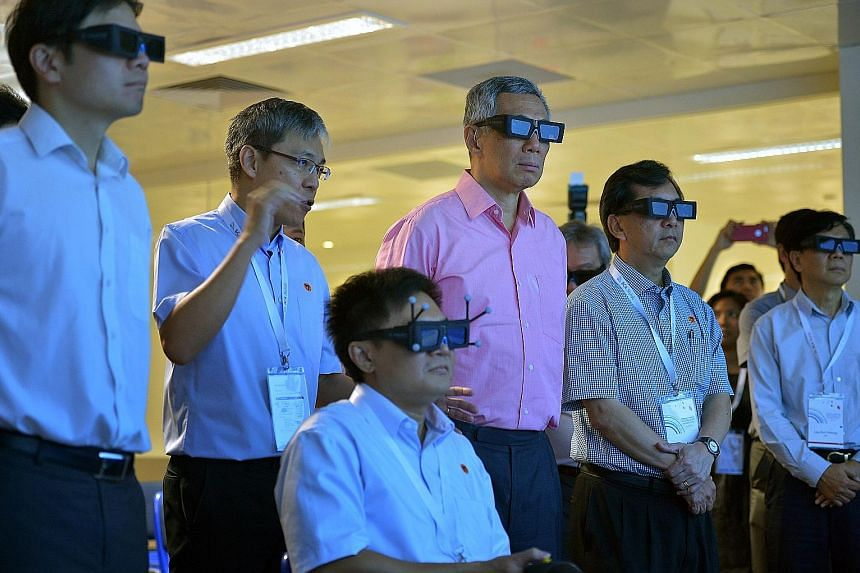 PM Lee taking a virtual tour of Changi Airport's upcoming Project Jewel at the BCA's Centre for Lean and Virtual Construction yesterday with BCA chief executive John Keung (second from right) and National Development Minister Lawrence Wong (far left)