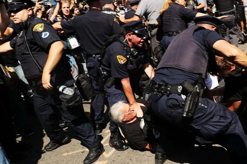 Protesters clash with policemen after trying to burn an American Flag near the site of the Republican National Convention in Cleveland on July 20.