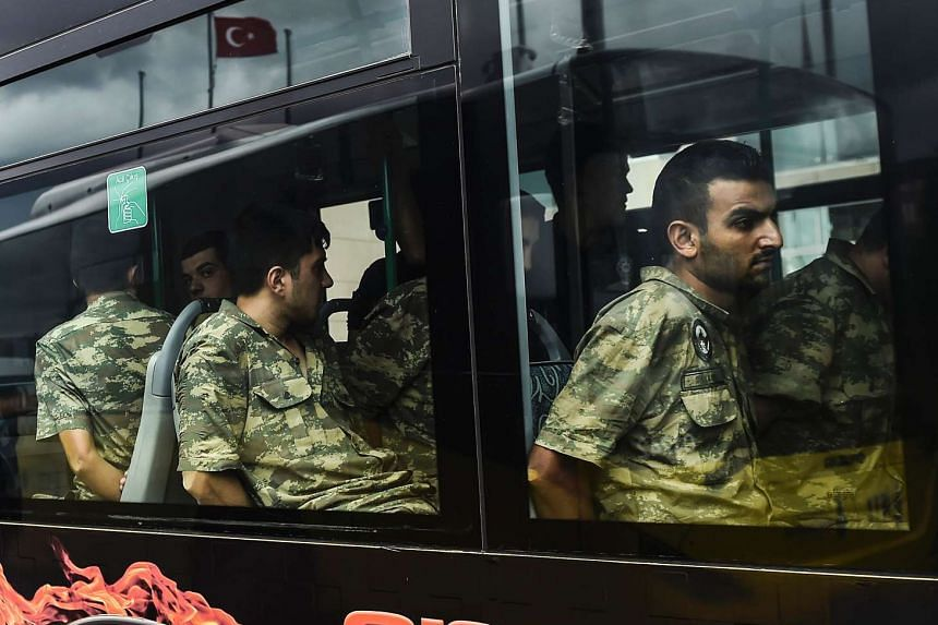 Detained Turkish soldiers who allegedly took part in a military coup arrive in a bus at the courthouse in Istanbul on July 20, 2016.