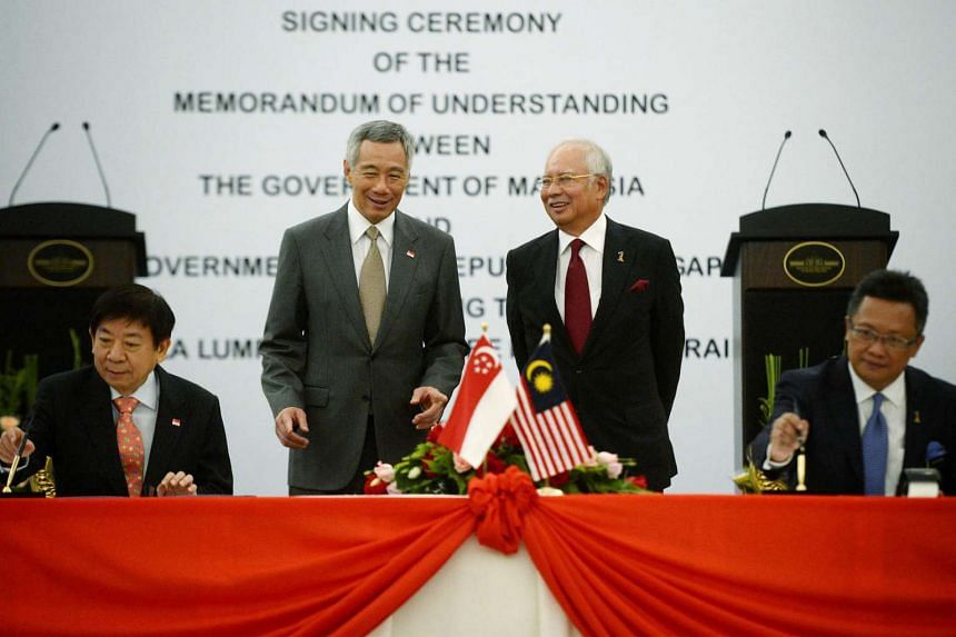 Prime Minister Lee Hsien Loong and Malaysian Prime Minister Najib Razak observe Singaporean Minister for Transport Khaw Boon Wan and Malaysian Minister in the Prime Minister's Department Abdul Rahman Dahlan as they sign the High Speed Rail MOU.