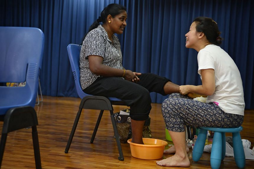 Malaysian cleaner Nagamah Jayaramm (above) gets to put her feet up and be pampered by volunteer Yunn Chee.