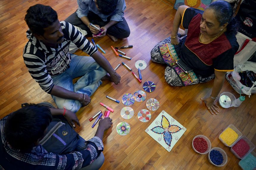 Some foreign workers learning to create Rangoli artwork from Ms Vijaya Mohan (right). Rangoli, a form of Indian floor art, is created with household items like pasta, rice grains and recycled utensils.