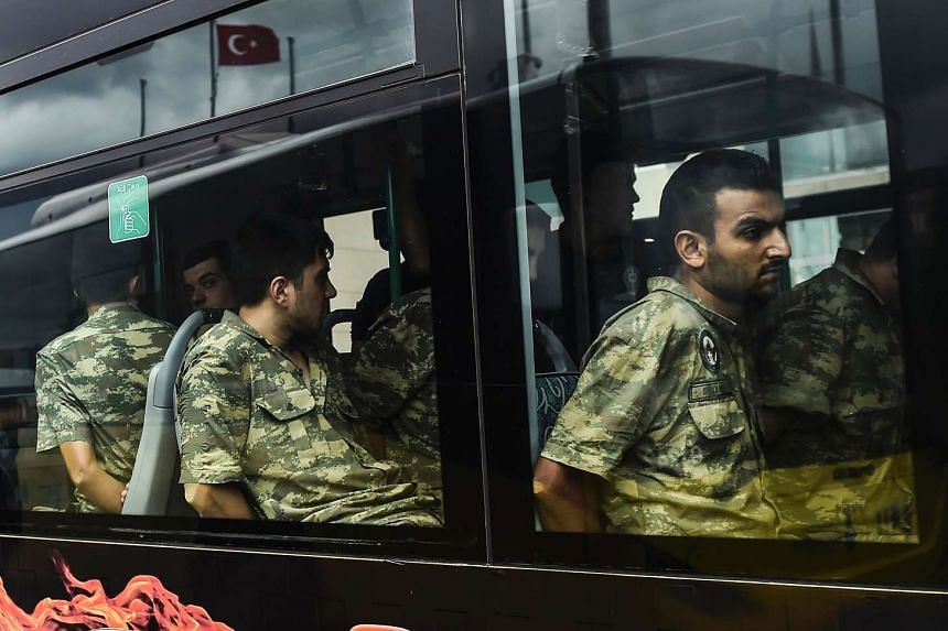 Detained Turkish soldiers who allegedly took part in last Friday's coup attempt arriving at the Istanbul courthouse yesterday. So far, about 9,300 people have been detained, including 118 generals and admirals accused of treason for allegedly masterm