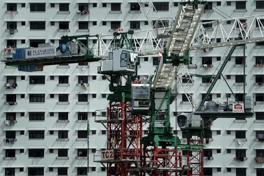 A crane operating at a construction site in front of a block in Sengkang on May 31.