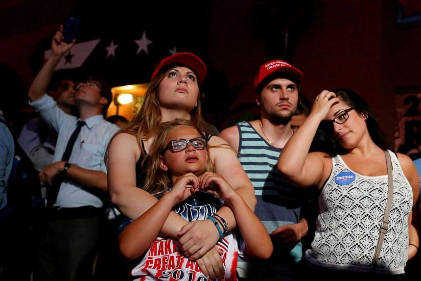 Supporters of Republican presidential candidate Donald Trump cheer as they watch him speak on a television in the street near the Republican National Convention in Cleveland, Ohio, July 21.