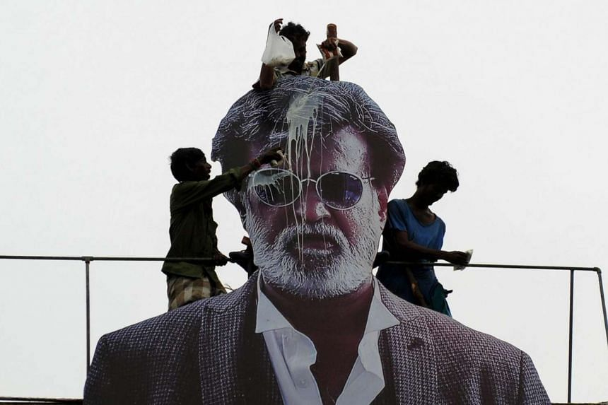 Indian fans pour milk to bless a cut-out image of Bollywood star Rajinikanth outside a cinema on the first day of release of his new Tamil language film Kabali in Chennai, on July 22, 2016.