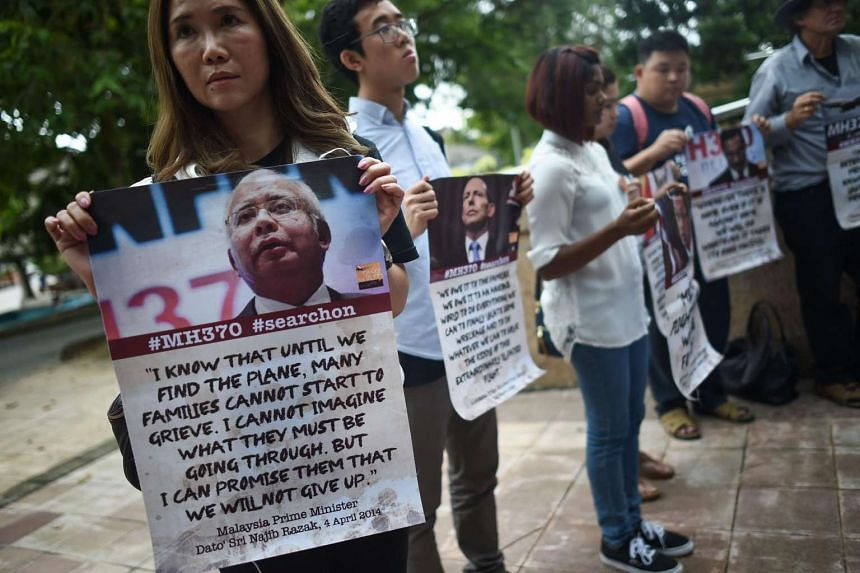Relatives of passengers on the missing Malaysia Airlines flight MH370 hold placards after a joint press conference in Putrajaya, on July 22, 2016.