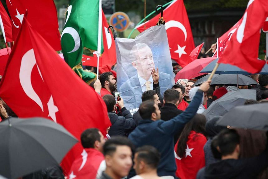 Members of Germany's Turkish community gathering in front of the Turkish Consulate in Hamburg on July 16, 2016, to protest against a military coup attempt in Turkey.