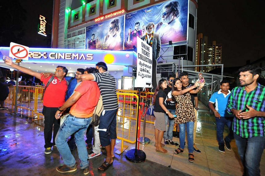 Fans take photos with the posters of Tamil superstar Rajinikanth outside Rex Cinema at Mackenzie Road, on July 22, 2016.