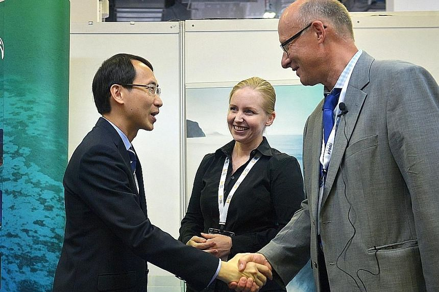 Mr Goh of the EDB greets Dr Ole Svenstrup Peterson, the incoming director of R&D at DHI Singapore. With them is Ms Groen, DHI's managing director. The Danish water and environmental firm is set to expand its R&D centre here.