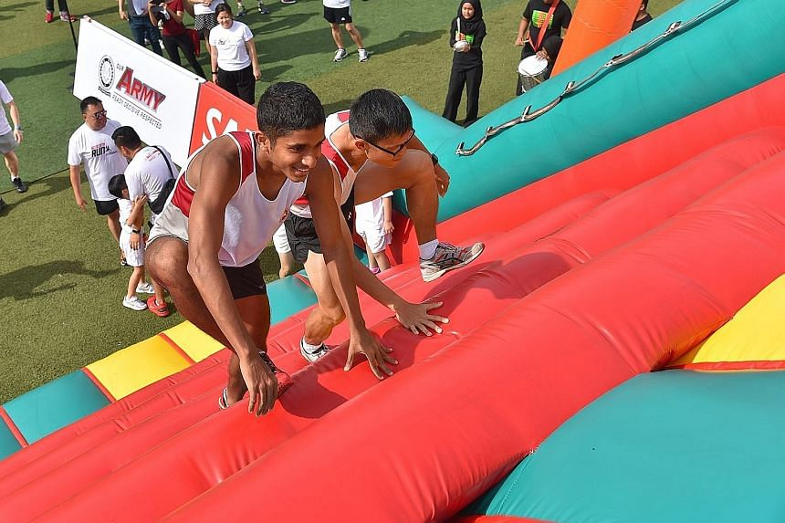 Runners Devathas and Lim Xiang, who will be taking part in the 21km Army Half Marathon on Aug 28, trying out the inflatable Apex Ladder, a new feature inspired by the SAF's Standard Obstacle Course at this year's Safra Singapore Bay Run and Army Half