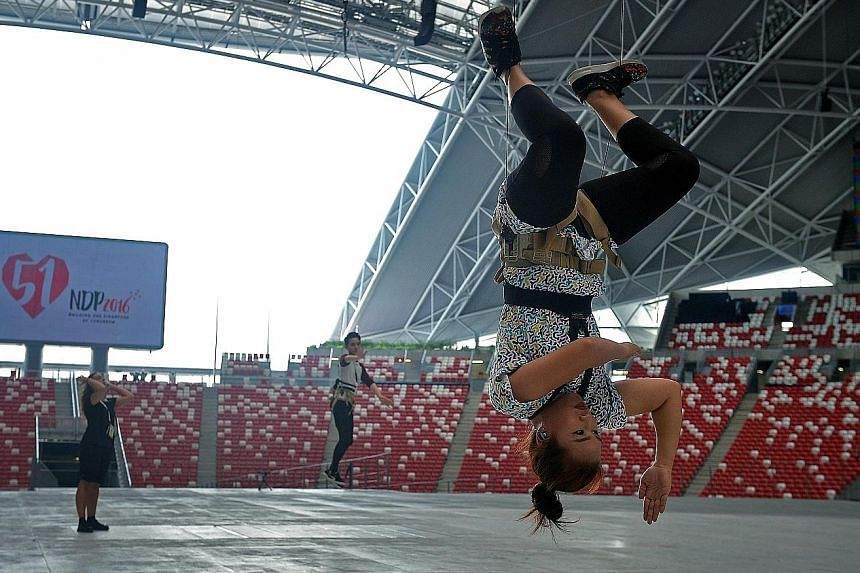 Above: Aerialists Wayne Wee, Rajid Ahamed and Biwa Mastura Mohamed Said have undergone intensive training since May. Above left: Ms Biwa and the MDC unit rehearsing at the National Stadium for the first time.