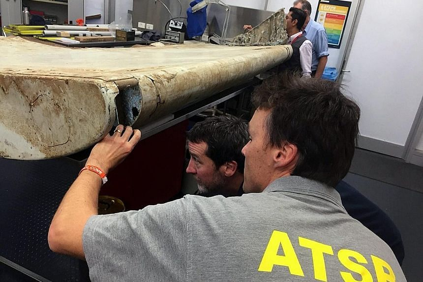 Malaysian and Australian investigators in Canberra (left and below) examining a piece of aircraft debris found on Pemba Island off the coast of Tanzania. It is believed to be an outboard wing flap belonging to Malaysia Airlines flight MH370.