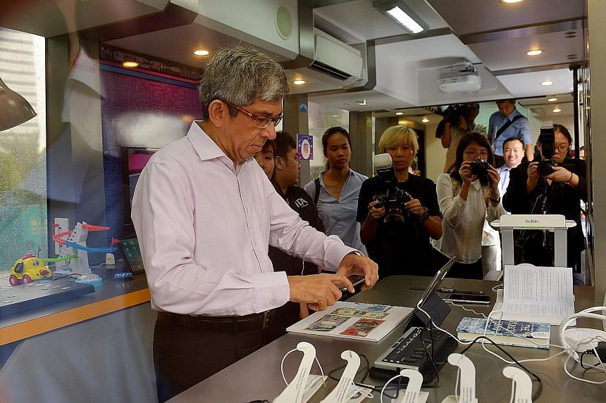 Dr Yaacob trying a money reader app yesterday inside the mobile IDA Lab at the E² Connect forum and exhibition.