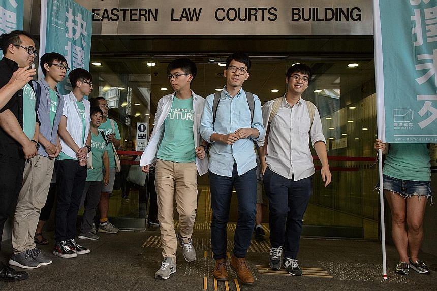 Pro-democracy activists (from left) Joshua Wong, Nathan Law and Alex Chow leaving the court in Hong Kong yesterday. Wong and Chow were found guilty of unlawful assembly, while Law, who is hoping to win a seat in the legislature in the September elect