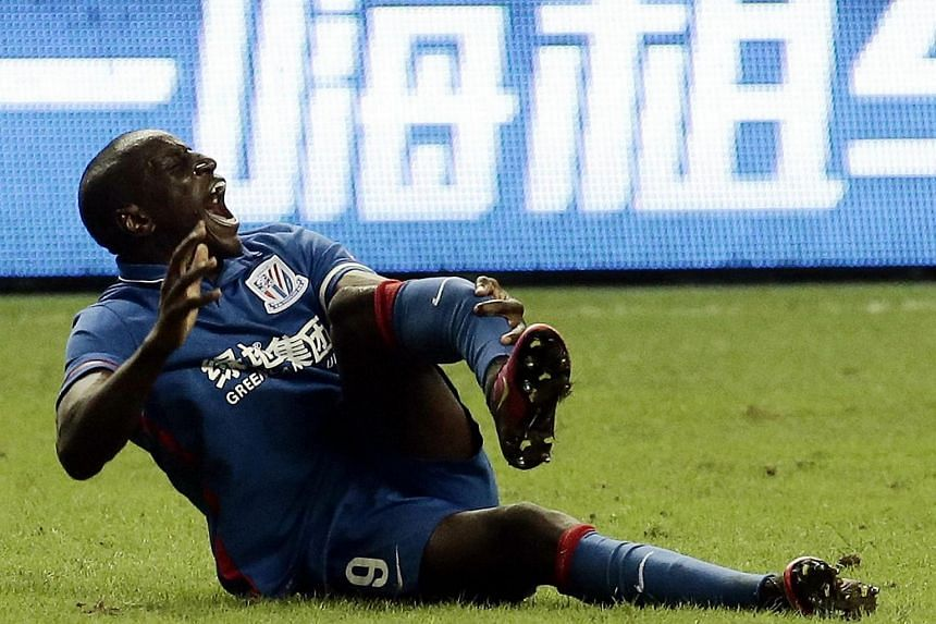 Demba Ba of Shanghai Shenhua reacting moments after breaking his leg during the 17th round football match of the Chinese Super League against Shanghai SIPG in Shanghai.