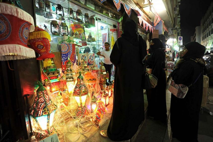 Saudi women shop for traditional lanterns at a market in the city of Jeddah on June 3, 2016.
