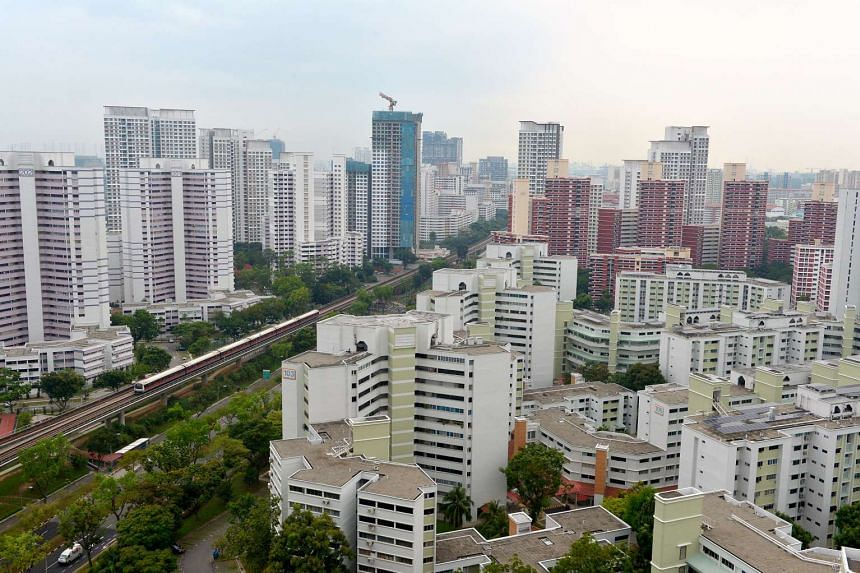 An MRT train travelling along the track among blocks of housing flats in Bukit Batok Central.