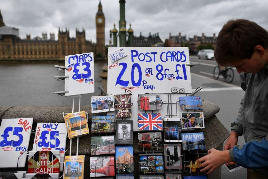 London themed postcards, including some depicting the Union flag, are displayed for sale near the Houses of Parliament in central London on June 29, 2016.