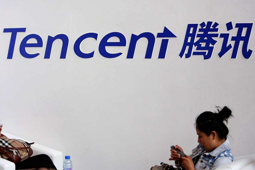 Visitors use their smartphones underneath the logo of Tencent in Beijing, on May 6, 2014.
