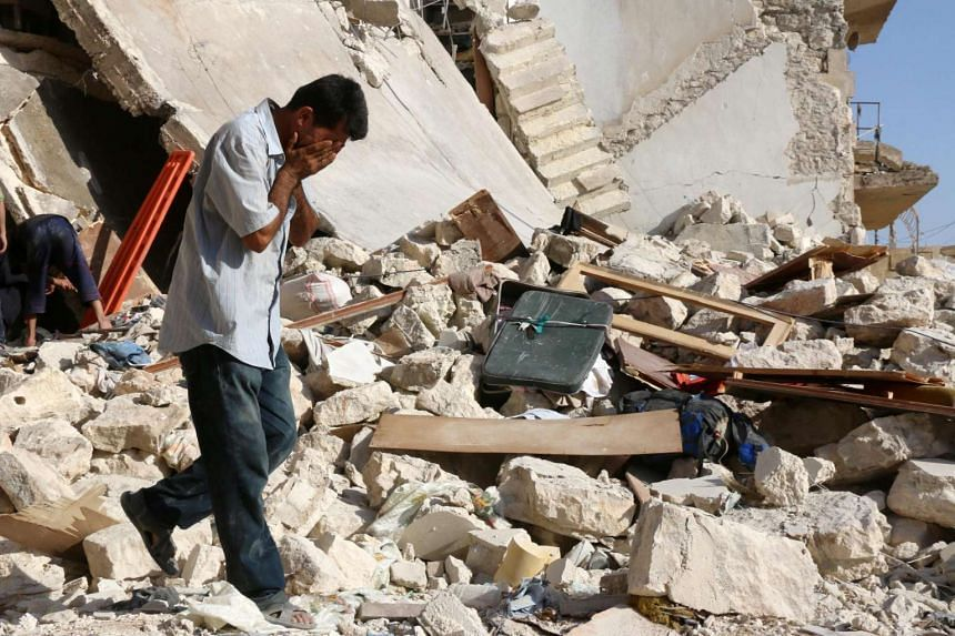 A Syrian man reacts as rescuers look for victims under the rubble of a collapsed building following a reported air strike on the rebel-held neighbourhood of Sakhur in Aleppo on July 19, 2016.
