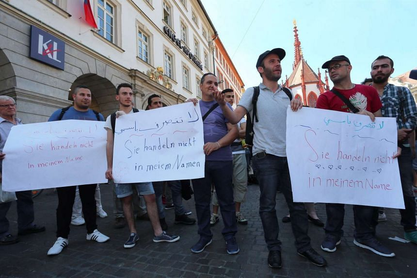 """Refugees, some of whom come from Syria, and their supporters demonstrate with posters written with """"They aren't acting in my name"""" in downtown Wuerzburg, Germany on July 20, 2016."""