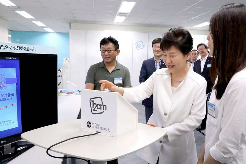 South Korean President Park Geun Hye tries out a mobile coupon transaction at a visit to a tech startup in the Creative Economy Valley in Pangyo, on July 21, 2016.
