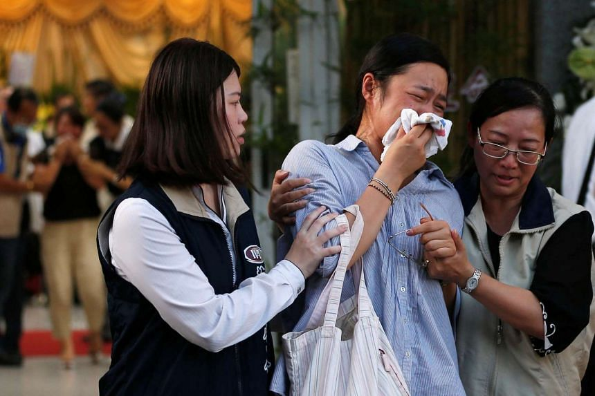Family members of victims who died in a bus accident near Taoyuan International Airport, cry as they attend a funeral on July 21, 2016.