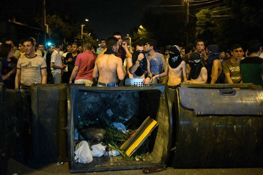 Armenian opposition supporters are seen behind barricades as they clash with riot police blocking the streets to Erebuni police station, where gunmen are holding hostages, in Yerevan late on July 20, 2016.