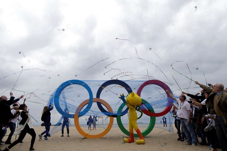 The 2016 Rio Olympics mascot Vinicius (centre) attends the inauguration ceremony of the Olympic Rings placed at Copacabana Beach in Rio de Janeiro, on July 21, 2016.