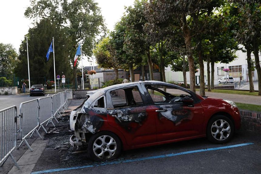 A burned car in front of the city hall of Beaumont-sur-Oise, northern suburbs of Paris, on July 21 2016.