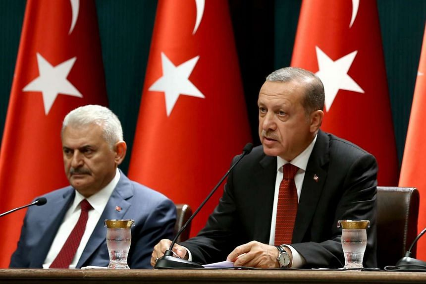 Turkish President Recep Tayyip Erdogan (right) delivers a speech at a press conference on July 22, 2016, flanked by Turkish Prime Minister Binali Yildirim.