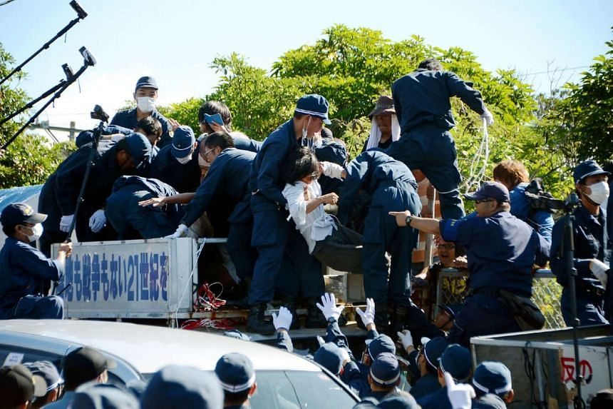People protesting against restarting the construction of helipads for US forces clash with riot police in Higashi-son, Okinawa prefecture, on July 22, 2016.