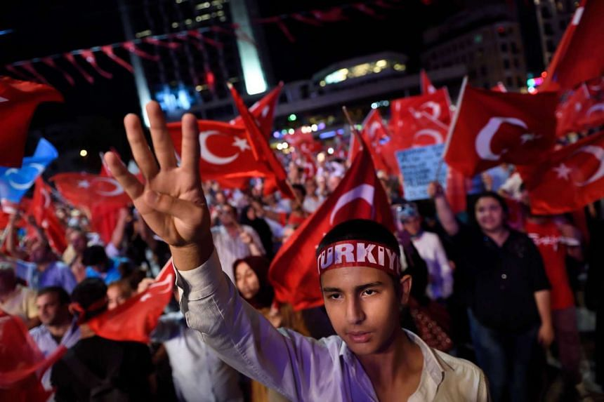 Erdogan supporters wave Turkish flags as they gather on July 21, 2016, during a rally in Istanbul.