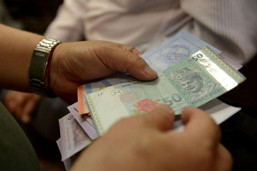 A person counting Malaysian ringgit notes.