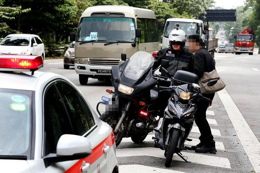 Staff Sgt Pan Jian Hong (left), 33, booking a motorcyclist for speeding along the BKE yesterday. The staff sergeant was riding one of the Traffic Police's new unmarked motorbikes.