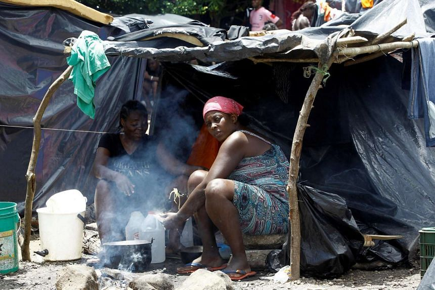 Two African migrants stranded in Costa Rica cook food in their tent at a makeshift camp at the border between Costa Rica and Nicaragua.