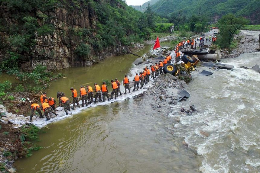 Chinese soldiers carrying sandbags to reinforce a damaged road hit by heavy rainstorms in Fangshan District in Beijing on July 21.