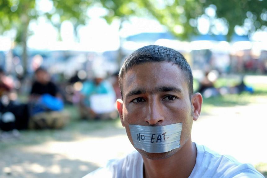 A migrant protests in a park before he starts walking with others on their way to Hungary in Belgrade, Serbia, July 22, 2016.
