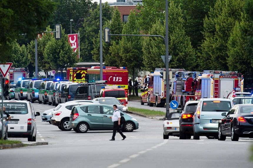 Police and firefighters are seen near a shopping mall amid a shooting on July 22, 2016 in Munich.