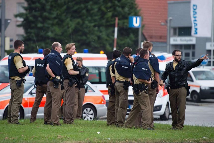 Police walk towards a shopping mall amid a shooting on July 22, 2016 in Munich.