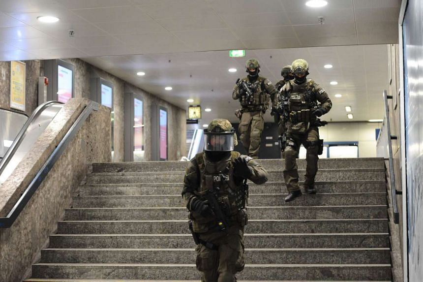 Police walk inside a subyay station Karlsplatz (Stachus) near a shopping mall following a shooting on July 22, 2016 in Munich.