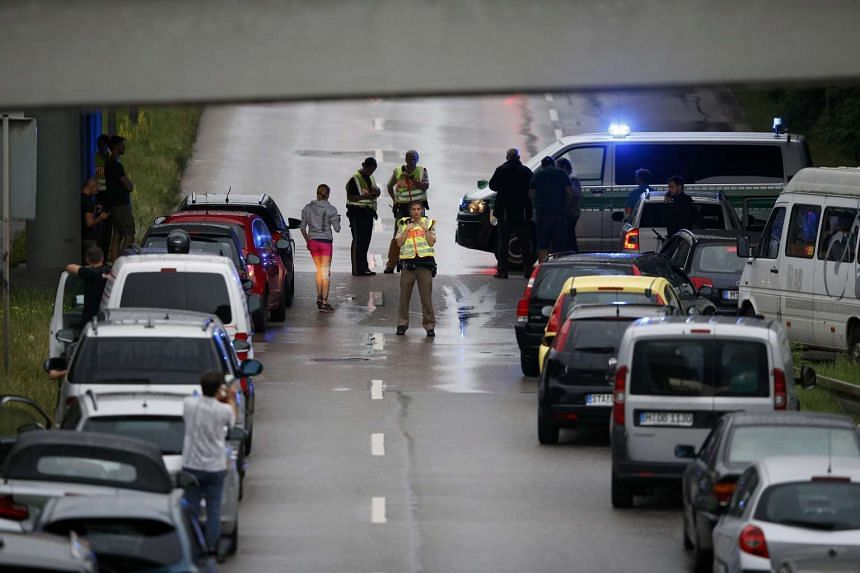 Police halt traffic on a road near to the scene of a shooting rampage at the Olympia shopping mall in Munich, Germany July 22, 2016.