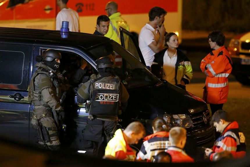 Special force police officers stand in front of a car near the Olympia shopping mall, following a shooting rampage at the mall in Munich, Germany on July 23.
