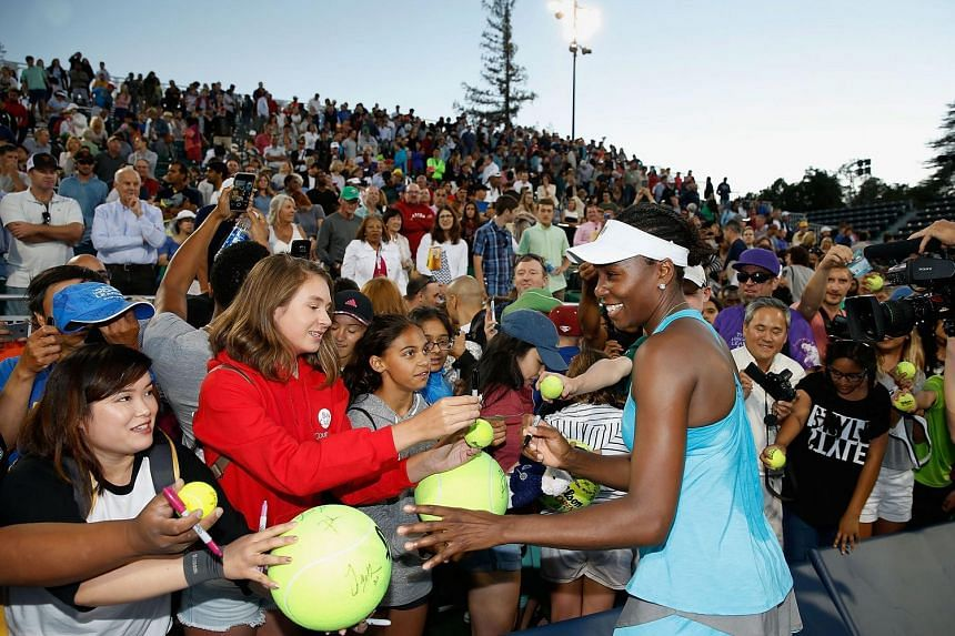 Venus Williams signs autographs for fans after a win against Catherine Bellis at the Bank of the West Classic, on July 22, 2016.