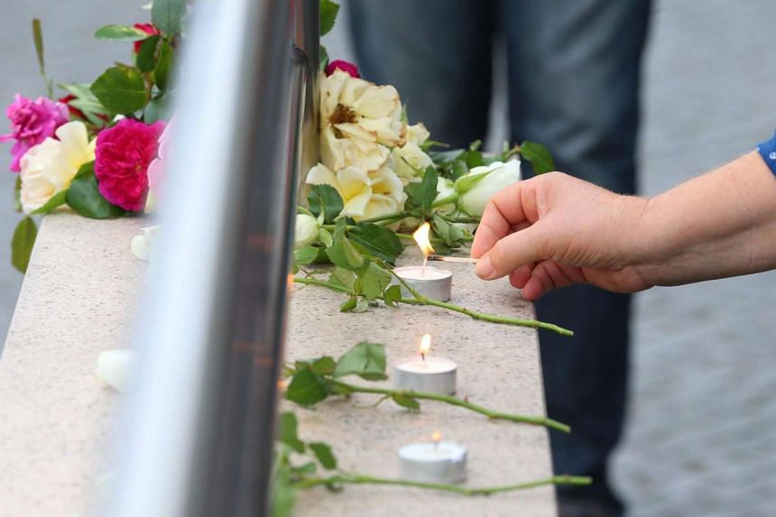A woman lights candles next to flowers placed at an entrance to the underground station of Olympia shopping centre in Munich, on July 23, 2016.