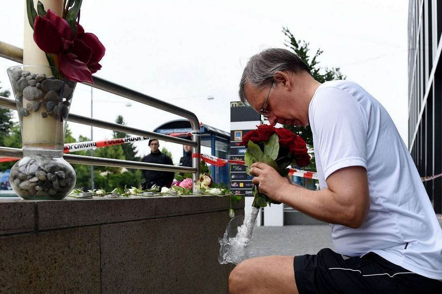 German citizen Thomas Tirolf brings flowers to commemorate victims on the street near the shopping mall Olympia Einkaufzentrum in Munich on July 23, 2016.