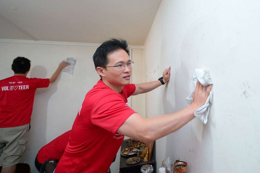 Young NTUC executive secretary Desmond Choo cleans one of the homes in Block 299B Tampines St 22.