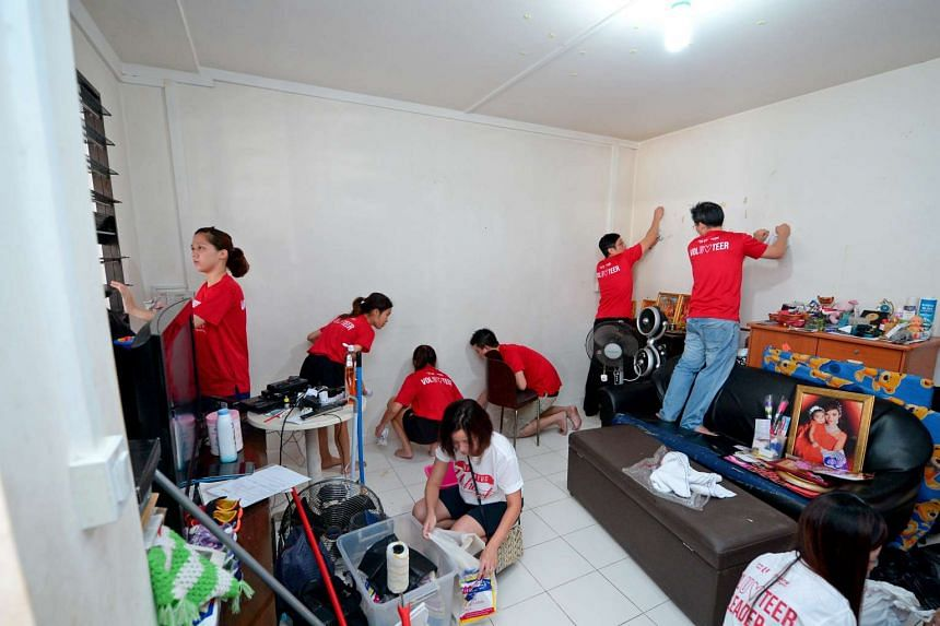 Young NTUC volunteers clean one of the homes in Block 299B Tampines St 22, with North East Community Development Council Mayor Teo Ser Luck (2nd from right) and Mr Desmond Choo (far right).