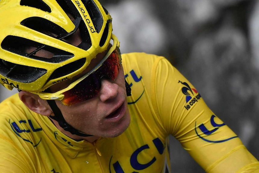 Chris Froome, wearing the overall leader's yellow jersey, rides in the rain during the 20th stage.